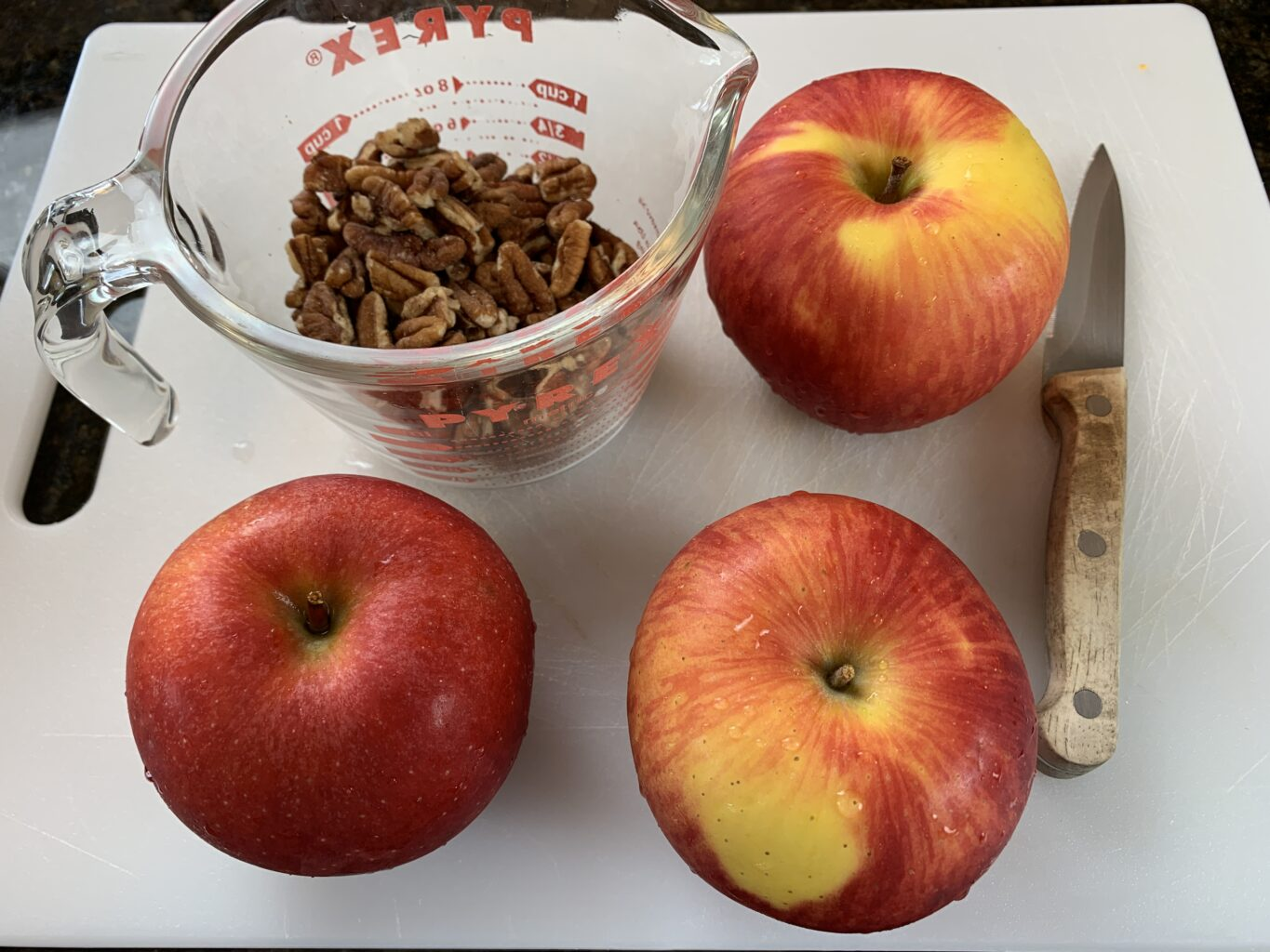 Apples, nuts and knife on cutting board