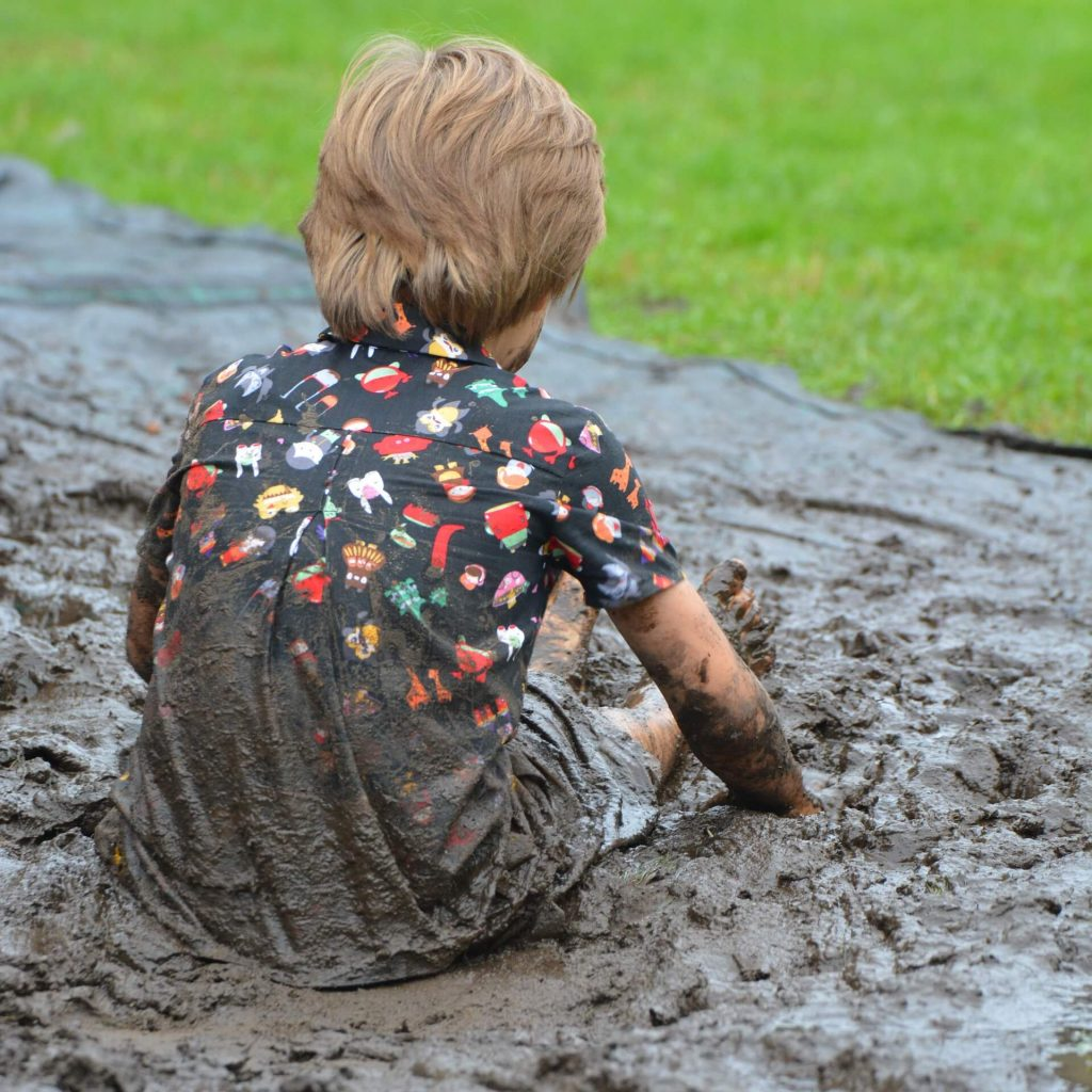 Child playing in the mud. Here's how to laugh more.