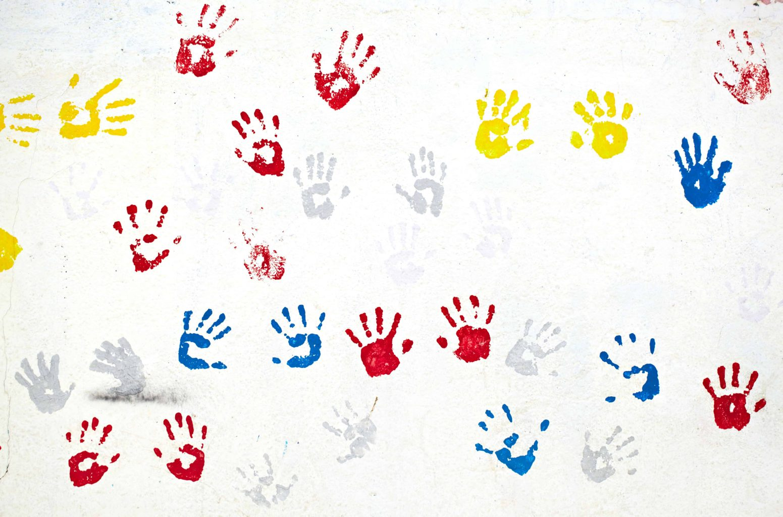 Graffiti with multiple colored hand prints on the white wall